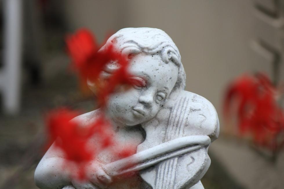 Angel sculpture behind flowers