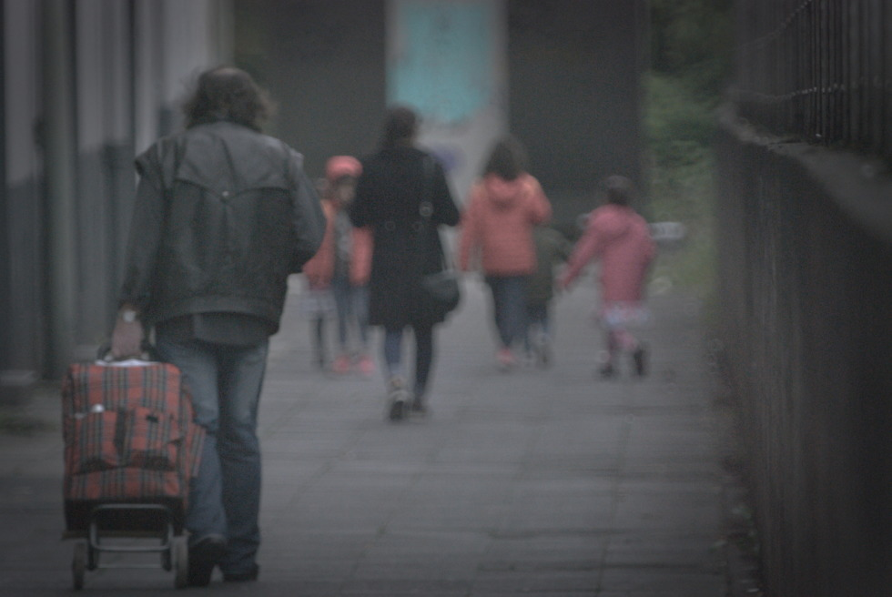 Man with shopper walking behind family