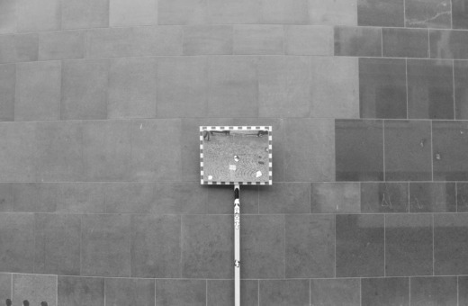 Traffic mirror in front of a big wall