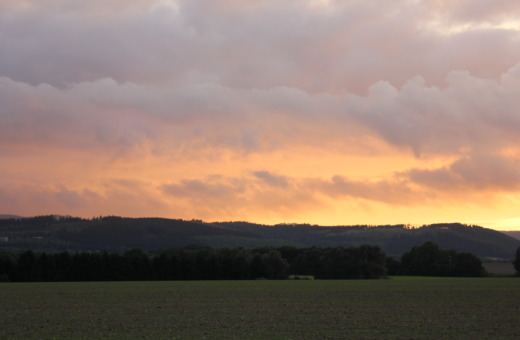 Burning sky over green fields