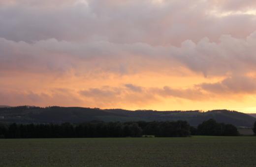 Burning sky over green fields