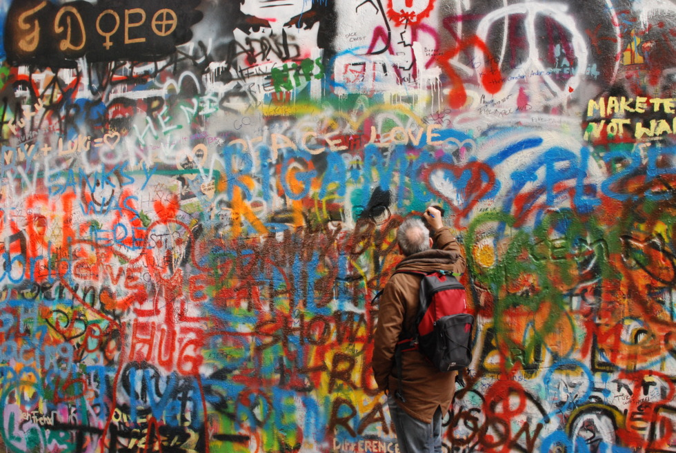 Guy painting on John Lennon wall