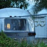 Airstream camper behind a hedge