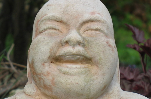 Face of a laughing Buddha made of clay
