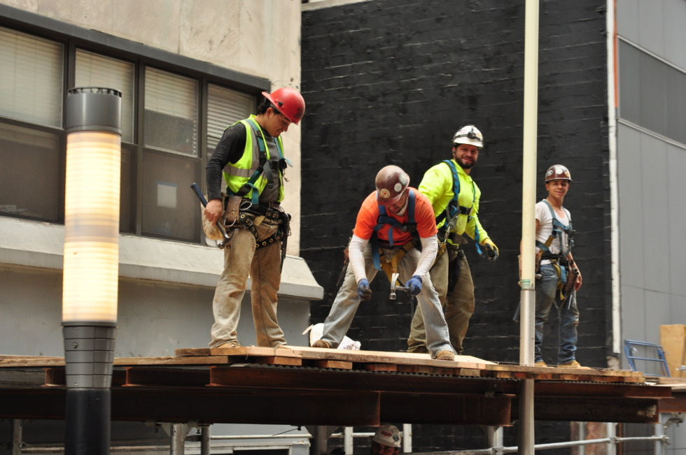 Four construction workers on a canopy in New York
