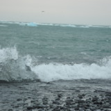 Ice block in the sea breaking a wave